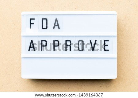 White lightbox with word fda approved on wood background