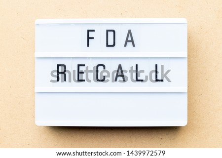 White lightbox with word fda recall on wood background