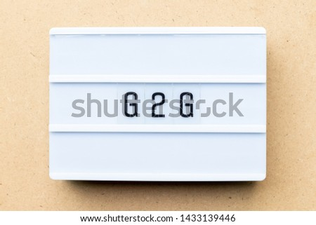 White lightbox with word G2G (abbreviation of Government to government) on wood background