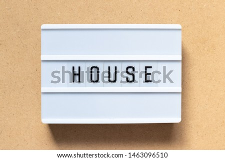 White lightbox with word house on wood background