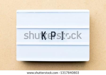 White lightbox with word KPI (Abbreviation of key performance indicator) on wood background