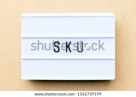 White lightbox with word SKU (abbreviation of stock keeping unit) on wood background