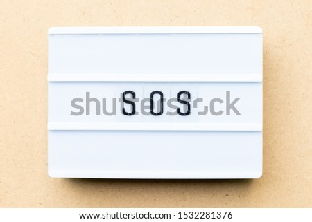 White lightbox with word SOS (abbreviation of save our soul/ship or sibling over shoulder) on wood background