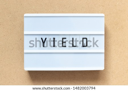 White lightbox with word yield on wood background