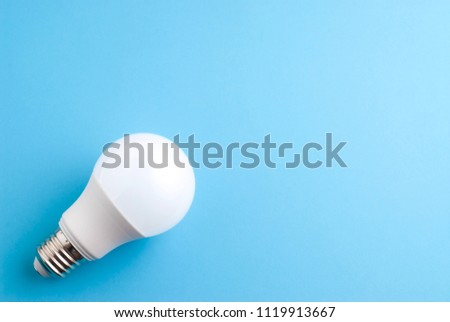 White lightbulb on blue background. Economical lightbulb. Neon light.