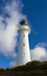 White lighthouse against deep blue sky.