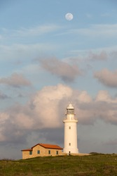 White lighthouse against the background of the evening sunset sky with clouds and a large moon. Paphos, Cyprus.