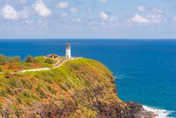 White lighthouse on cliff overlooking calm blue ocean