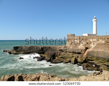 White lighthouse on the cliff with fortifications in Rabat