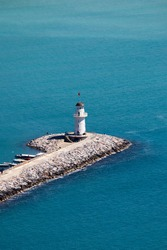 white lighthouse on the pier in Alanya port in Turkey surrounded by azure water of mediterranean sea