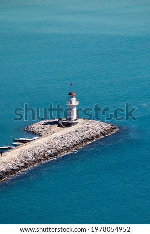 white lighthouse on the pier in Alanya port in Turkey surrounded by azure water of mediterranean sea Foto stock ©