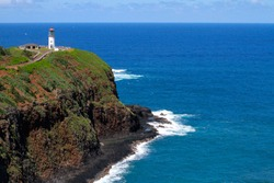 White Lighthouse set atop a cliff with a brilliant blue ocean in the background in Kauai, Hawaii, USA.