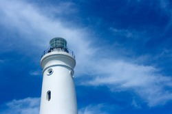White Lighthouse Tower With Cloudy Blue Sky