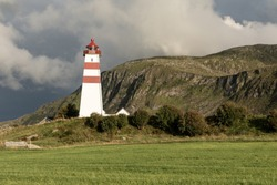 White lighthouse with red stripes in Norway. Norwegian scenic landscape with a tall white lighthouse. Lighthouse on the background of harsh Scandinavian nature. Alnes Lighthouse.  Alnes Fyr, Norway.