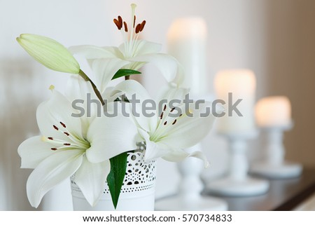Shutterstock White lilies in a vase against a backdrop of candles. Flowers. Postcard