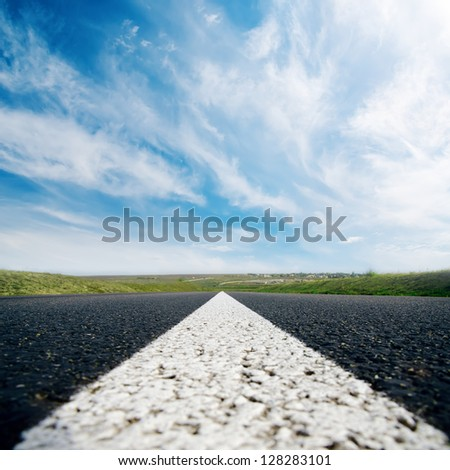 white line on asphalt road close up and cloudy sky