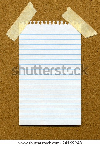 White lined blank paper stuck to a cork noticeboard.