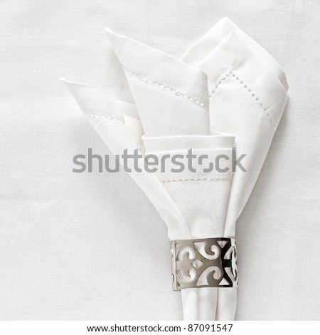 White linen napkin and silver napkin ring on as a table place setting