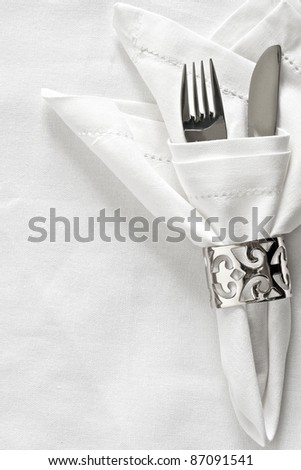 White linen napkin and silver napkin ring with cutlery