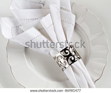 White linen table place setting with silver serviette ring