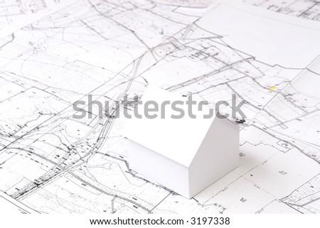 White little cardboard house model on building plan