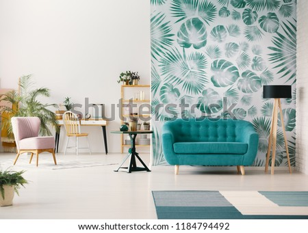 White living room interior with leafy wallpaper in the real photo with turquoise sofa, fresh plants, wooden desk and empty wall with place for your poster