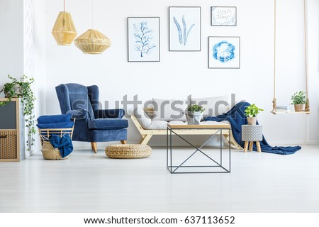 White living room wih navy blue armchair, sofa and posters #637113652