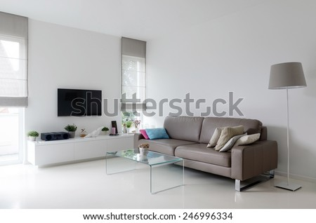 White living room with taupe leather sofa and glass table #246996334