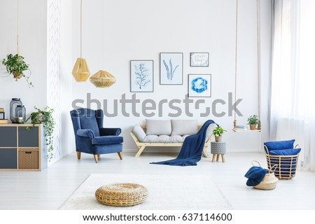 White living room with wood sofa, blue armchair, lamps, posters #637114600
