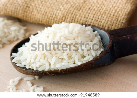 White long uncooked rice on wooden spoon