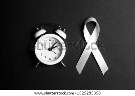White lung cancer awareness ribbon and alarm clock on black background. November lung cancer awareness month. Black and white image.