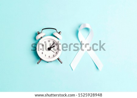 White lung cancer awareness ribbon and alarm clock on blue background. November lung cancer awareness month.
