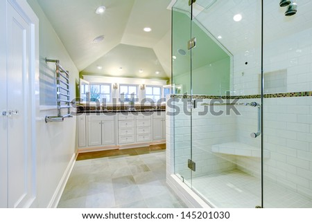White luxury bathroom cabinet with two sinks, vaulted ceiling and amazing shower.