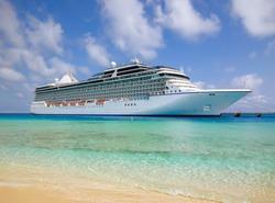 White luxury cruise ship docked in beautiful Caribbean sea close to the beach.