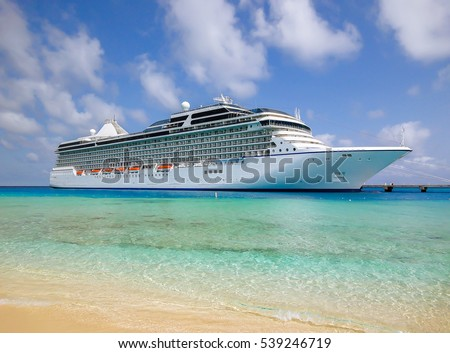 White luxury cruise ship docked in beautiful Caribbean sea close to the beach. #539246719