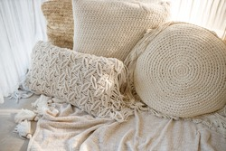White macrame pillows and knit blanket on the sofa. Scandinavian cozy home, details interior