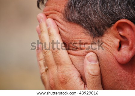 white man expressing tiredness and despair with his hands on his face