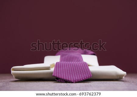 White man's shirt and lilac tie on a wooden table. Background burgundy. #693762379