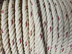 White manila rope has a large red stripe vertically woven into twine. or polypropylene rope wrapped in a circle Combined for convenient and neat use Often used to swing a boat or lift heavy objects.