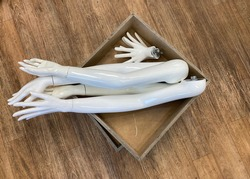 White Mannequin Arms and Hands in a Wooden Box on the Floor Seen From Above