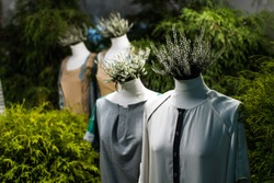 White mannequins , with heather on a dark green forest background. The concept of fashion, style, beauty, ecology, recycle, sustainability, reusing, concept. Zero and fabric waste, creative background