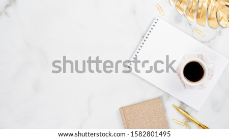 White marble home office desk table with paper notebook, golden pen and tropical monstera leaf, cup of coffee. Flat lay, top view, copy space. Feminine workspace concept. #1582801495
