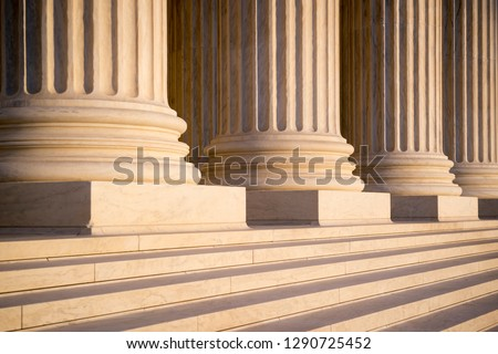 White marble neoclassical columns of the portico of the Supreme Court of the United States building in soft sunset light in Washington DC, USA #1290725452