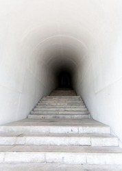 White marble staircase leading to dark tunnel