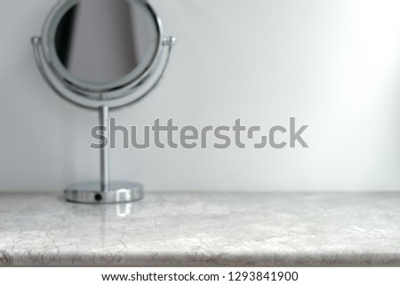 White Marble Table Top can used for display or montage your products. Selective focus blurred white background. Vanity Makeup Mirror.