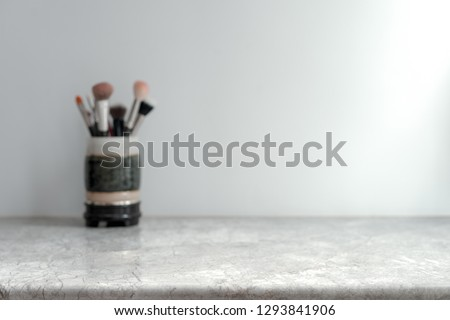 White Marble Table Top can used for display or montage your products. Selective focus blurred white background. Vanity Makeup Brushes.