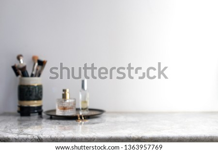 White marble table top can used for display or montage your products. Selective focus blurred white background. Vanity table makeup brushes perfume bottle spray.