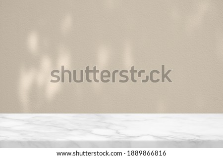 White Marble Table with Bokeh Light on Concrete Wall Texture Background in Set Sail Champagne Color Tone, Suitable for Product Presentation Backdrop, Display, and Mock up. Stock photo ©