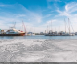 White marble table with the grey natural pattern, little shiny surface, perspective view, blurred background of sea bay with yachts, blue sky, empty space for product presentation.