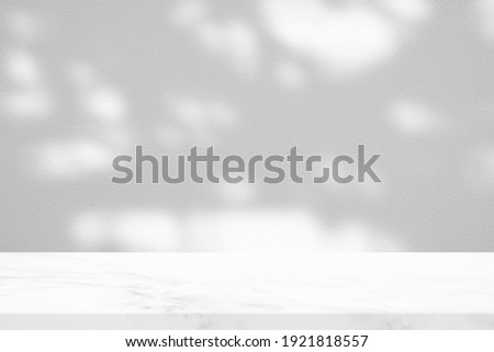 White Marble Table with Tree Shadow in the Garden on Concrete Wall Texture Background, Suitable for Product Presentation Backdrop, Display, and Mock up.